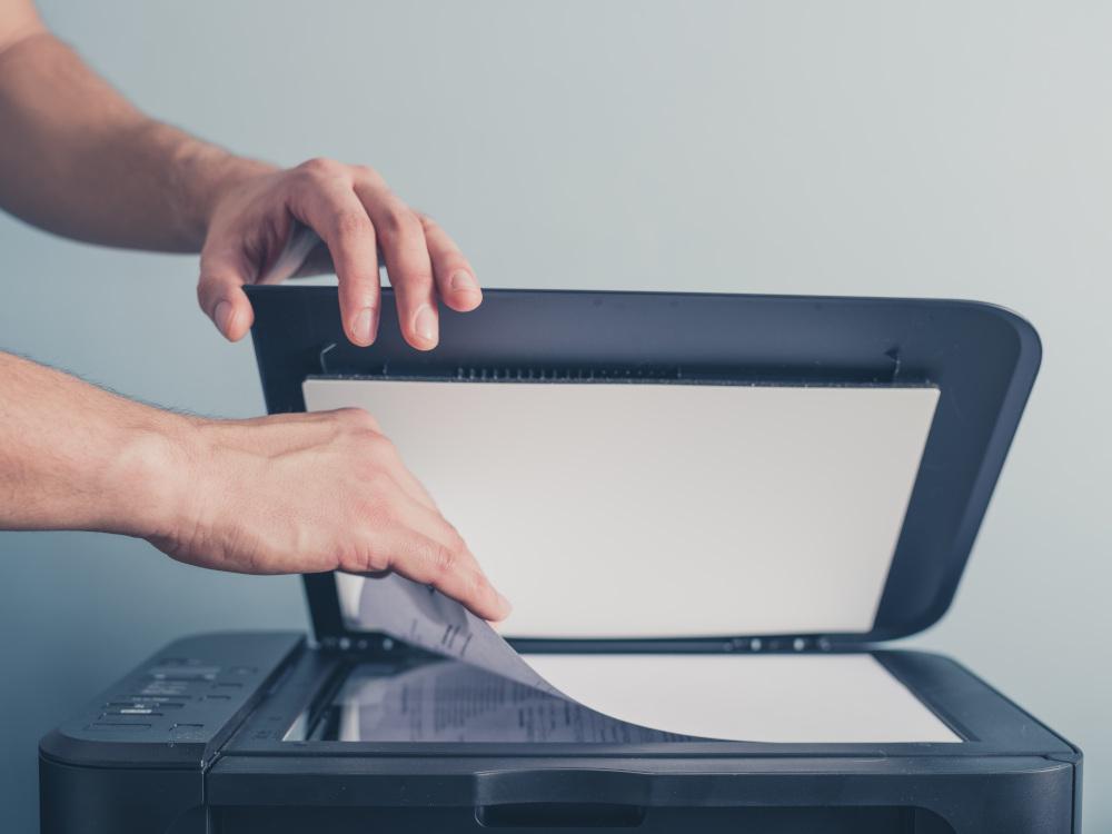 dłoń trzymająca pokrywę drukarki